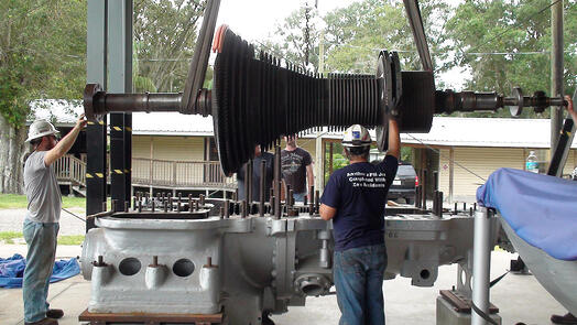 Image of Millwrights lowering large crankshaft into industrial machinery